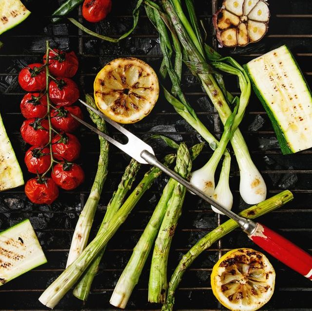 grilled vegetables green asparagus, garlic, lemon, spring onion, zucchini, cherry tomatoes, salad on bbq grill rack over charcoal top view barbecue concept photo by natasha breenredacouniversal images group via getty images
