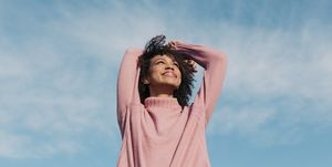 Portrait of happy young woman enjoying sunlight