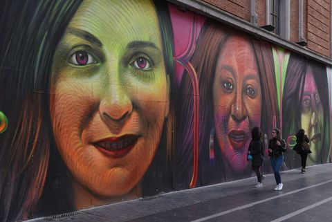 People seen walking next to a Change.org mural in Madrid.