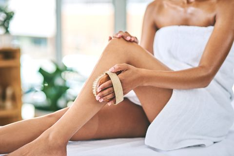 shot of a young woman exfoliating her legs with a brush