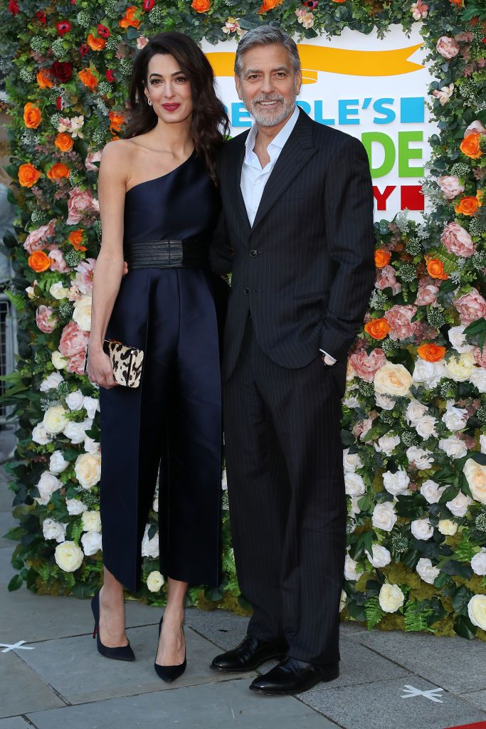 March 14, 2019 The couple attended the People's Postcode Lottery Charity Gala at McEwan Hall in Edinburgh, Scotland. For the occasion, Amal dressed up in a belted navy one-shoulder jumpsuit by Stella Mccartney and carried a cow print clutch while George looked handsome in a dark suit.