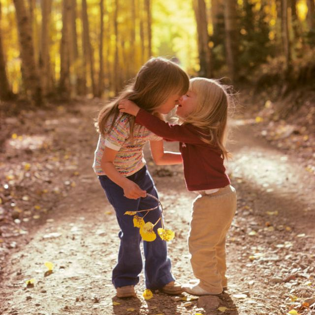 1970s two little girls sisters walking hugging in autumn woods on nature trail  photo by h abernathyclassicstockgetty images