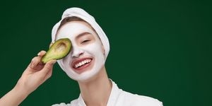 Cheerful girl with cosmetic mask on her face covering eye with avocado