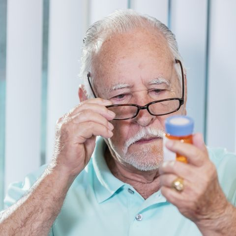 Senior man reading prescription medicine bottle