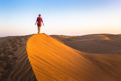 Girl walking on sand dunes in arid desert at sunset and wearing dress, scenic landscape of Sahara or Middle East