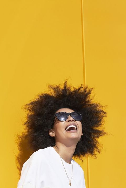 Carefree woman with yellow background