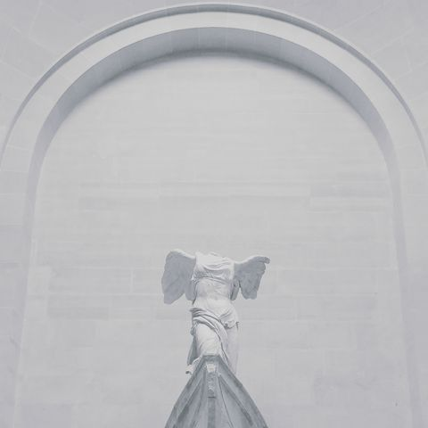 Low Angle View Of Broken Angel Statue Against White Building