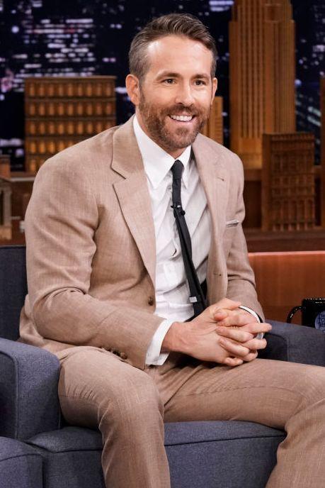Dress shirt, Collar, Trousers, Coat, Shirt, Suit trousers, Sitting, Outerwear, Formal wear, Suit,