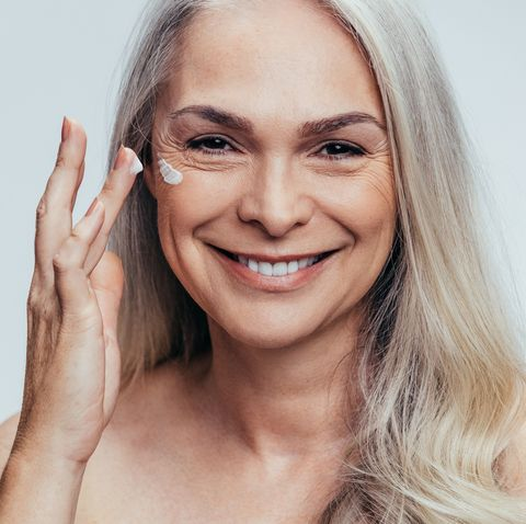 smiling mid adult caucasian woman applying anti aging cream on her face senior female woman applying moisturizer on her face against grey background
