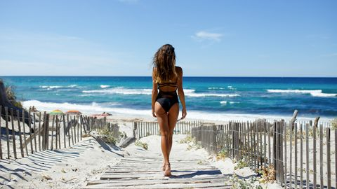 back view of a beautiful, brunette young girl, looking at ocean freedom concept, holiday, beach, clear sky background, light and shadow landscape scenery place