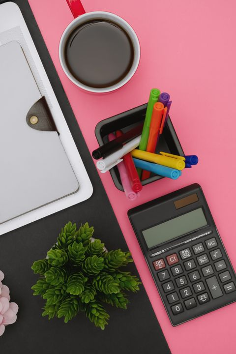 Laptop, Notepad and Office Supply Items over Pink Background