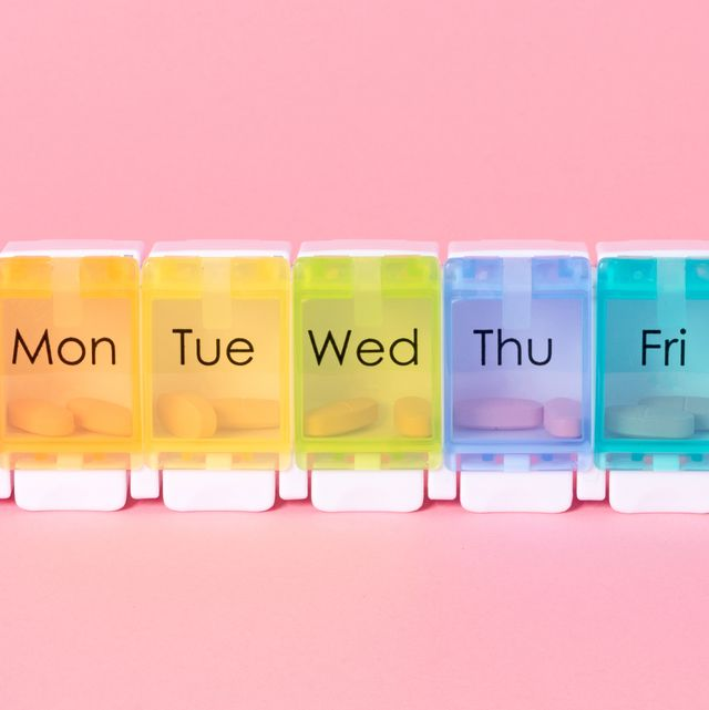 multi colored weekly pill organizer on pink colored background