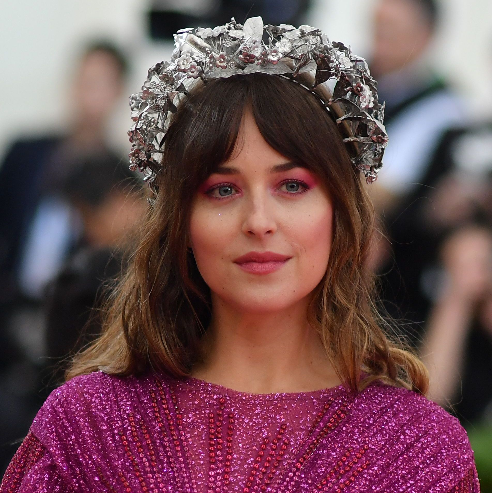 Dakota Johnson Johnson proved you can still look festive while keeping it simple: a Silver crown-headband dressed up her usual wavy hair while hot pink eyeshadow added some fun to her makeup look.