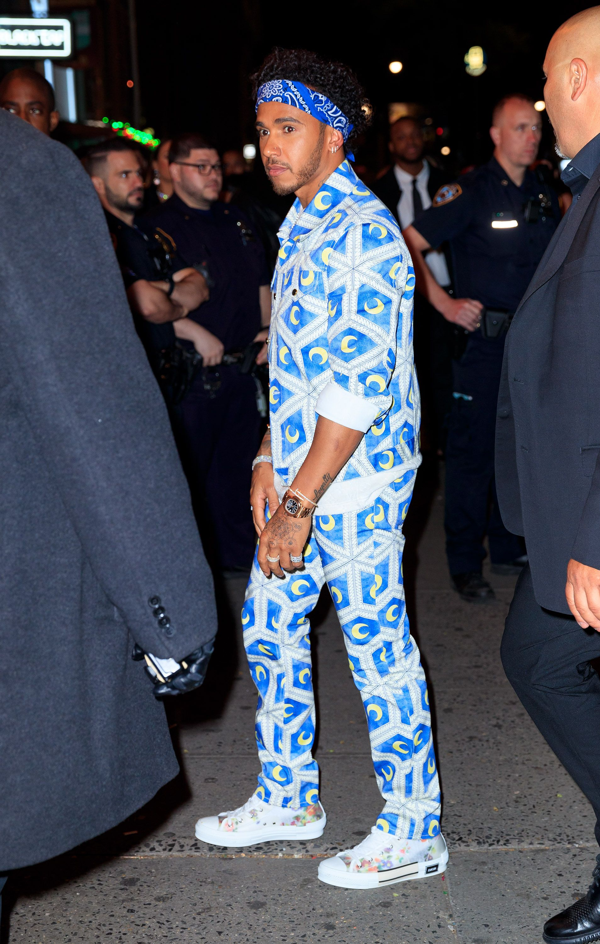 Lewis Hamilton Lewis Hamilton went sporty in a moon-printed tracksuit and sneakers with a blue bandana.