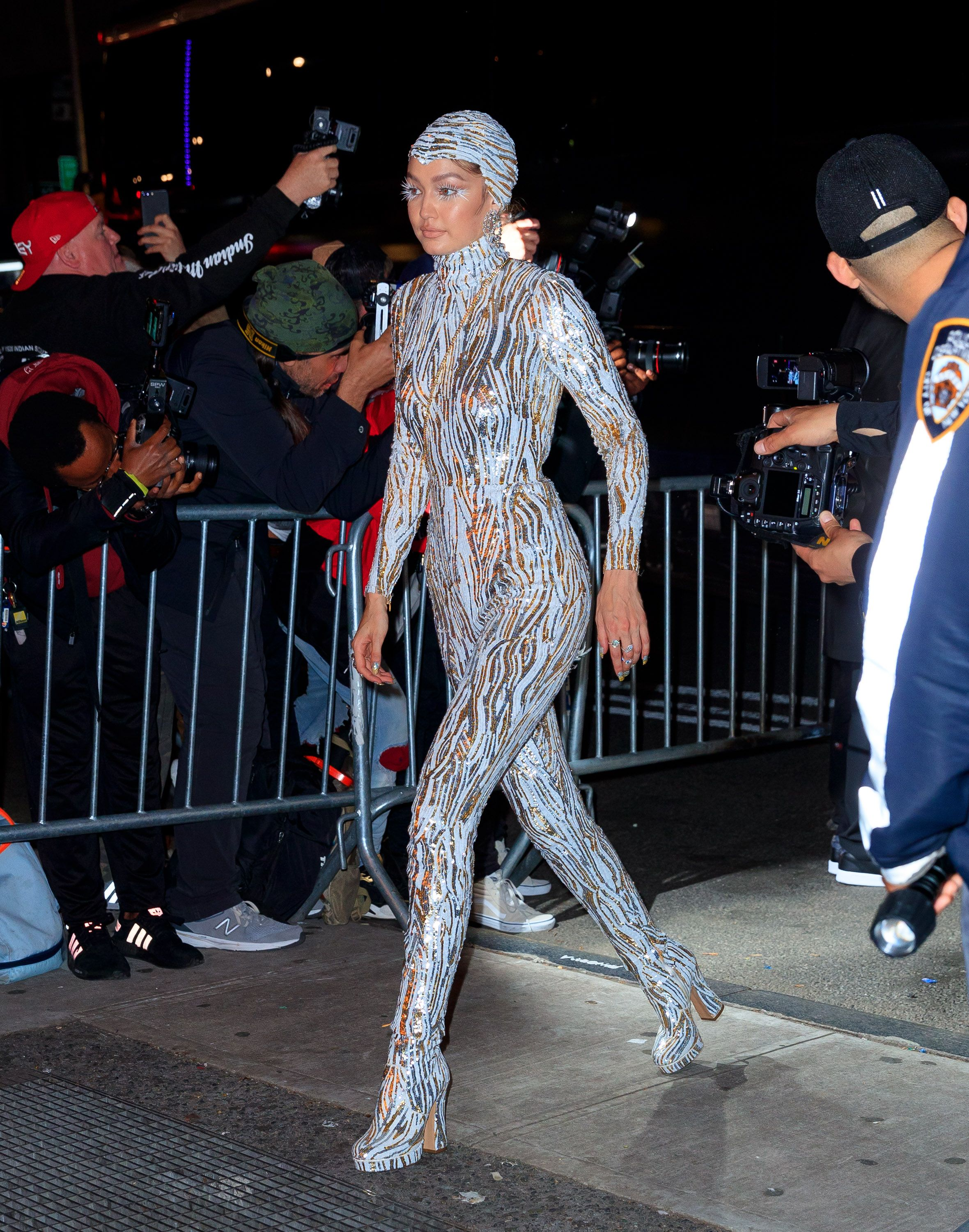Gigi Hadid Gigi removed the cape from her silver Michael Kors Met Gala ensemble to party it up in a catsuit and matching cap.