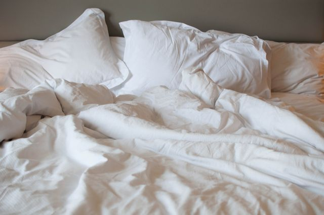 a close up view of messy bed with comforter and pillows