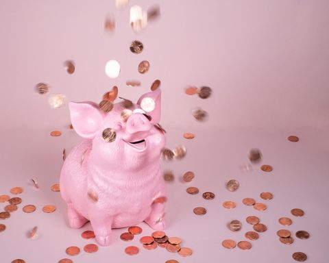 pink piggy coin bank on pink background with falling pennies