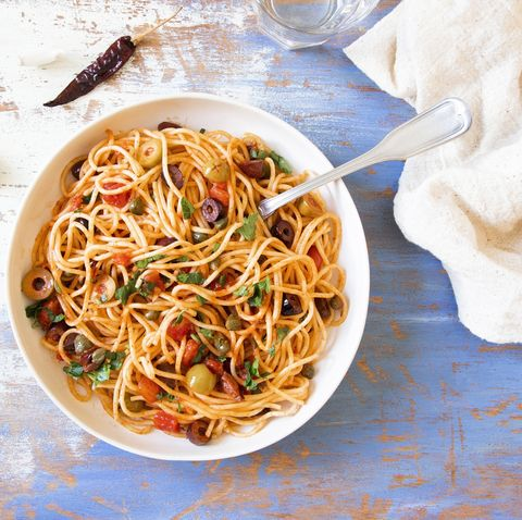 Traditional Itallian pasta spaghetti alla puttanesca with anchovies, tomatoes, olives, capers, garlic and parsley. T