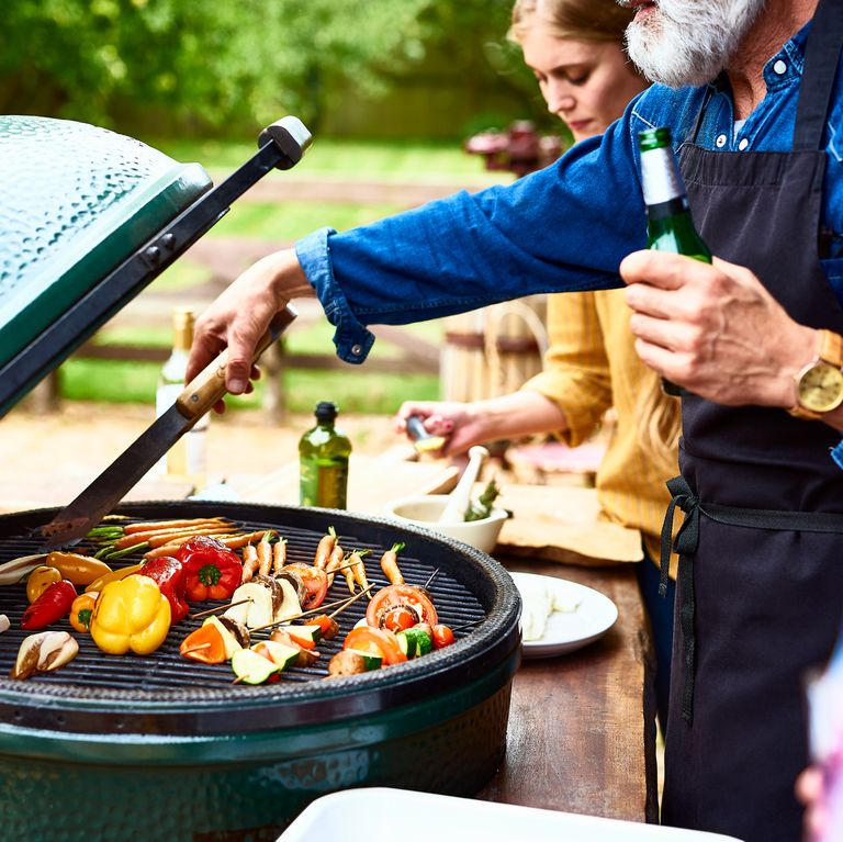 Man using tongues to turn vegetables on bbq