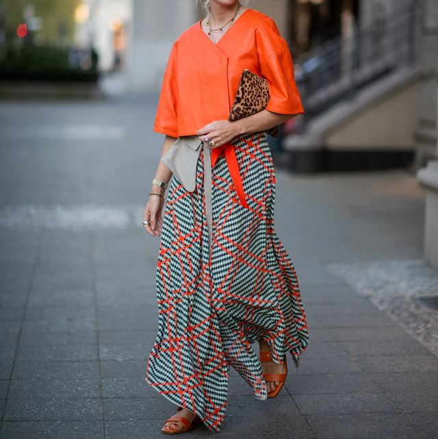 berlin, germany   april 25 cloudy zakrocki is seen wearing skirt with pattern, hat, orange top, sandals, prada clutch with leopard animal print on april 25, 2019 in berlin, germany photo by christian vieriggetty images