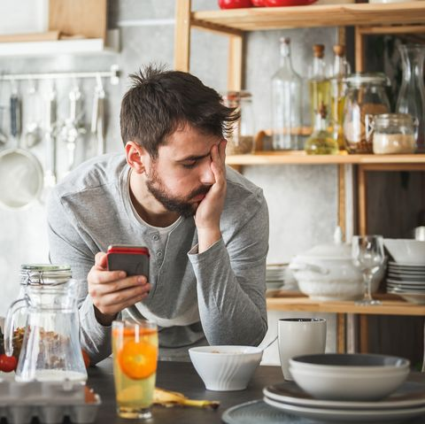 Sad man using smart phone during breakfast at home