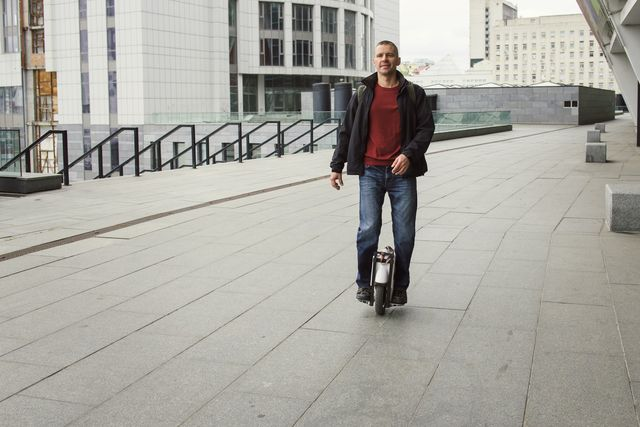 middle aged man riding on one wheel electronic device in the city male rider on one foot doing trick modern technologies for transportation gyroboard as a personal eco transport