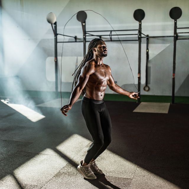 young african american athlete exercising with jump rope during sports training in a gym