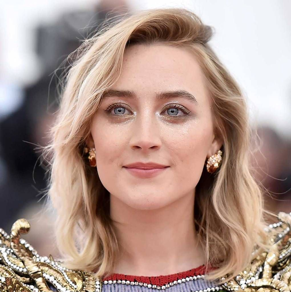 """Saoirse Ronan Ronan always goes pretty classic with her red carpet beauty looks—and this """"camp"""" themed event was no different. Her hair was a simple tousled lob with perfected skin, nude lips, and just a touch of glittery all around and below her eyes."""