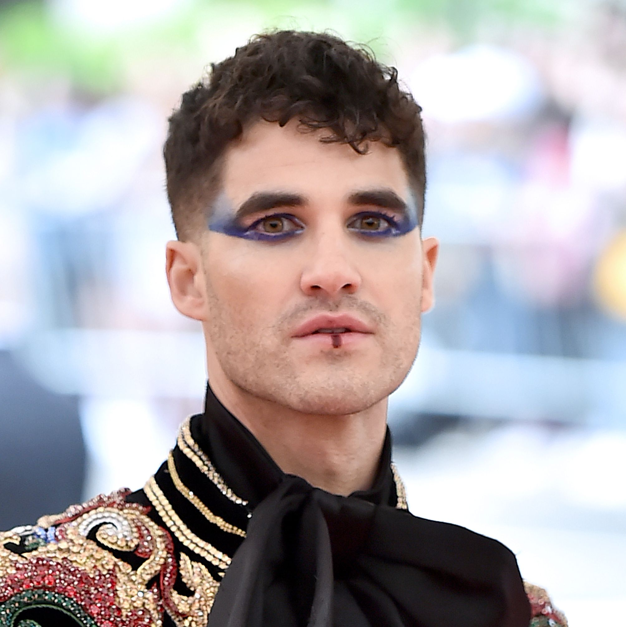 Darren Criss Criss embraced the theme in exaggerated blue eyeshadow winged out from under his eyes and a touch of color on his bottom lip.