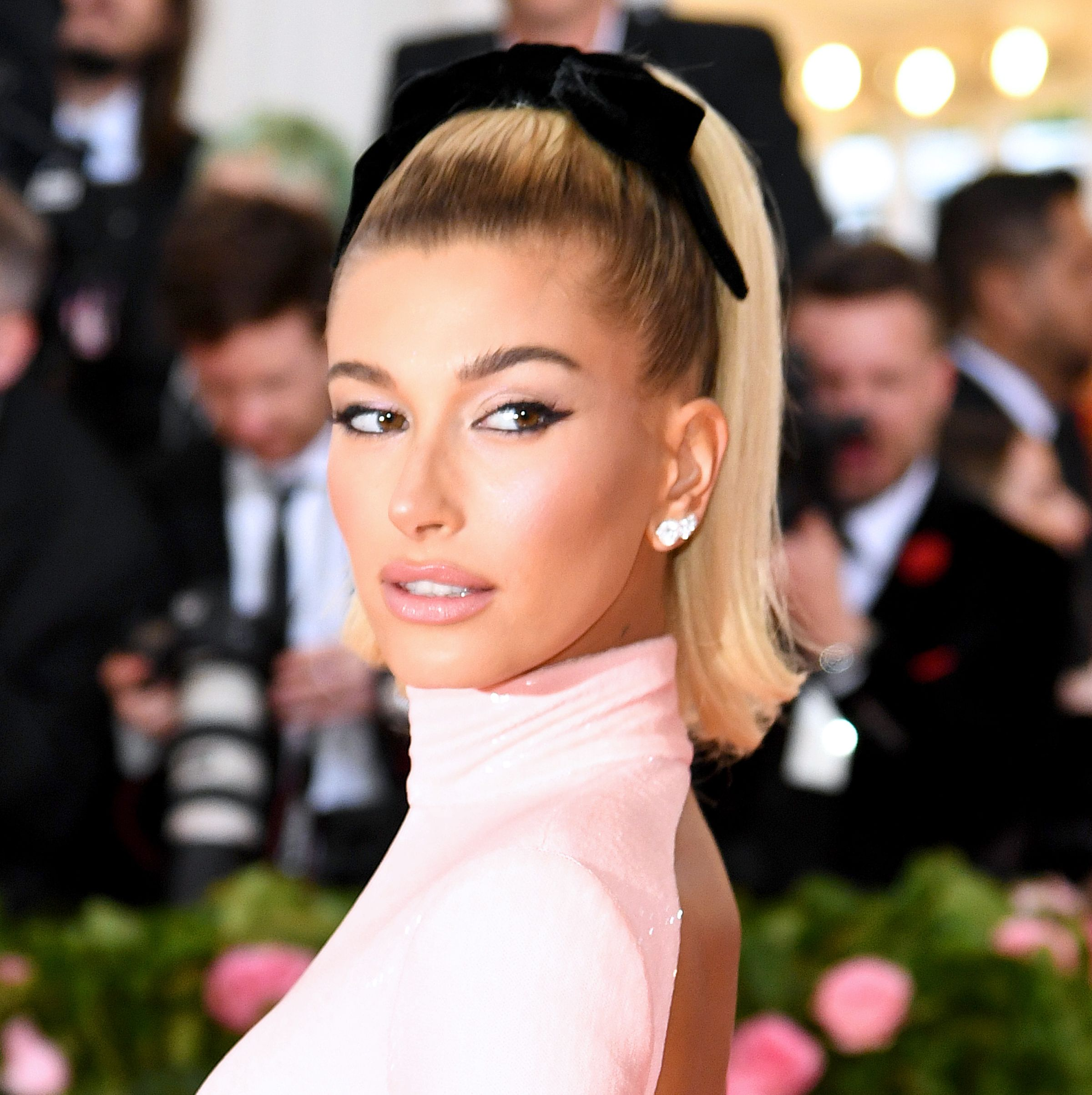 Hailey Bieber The model looked like a retro Barbie doll with a high, flippy blonde ponytail wrapped with a black velvet bow. Classic cat eyes finished the look.