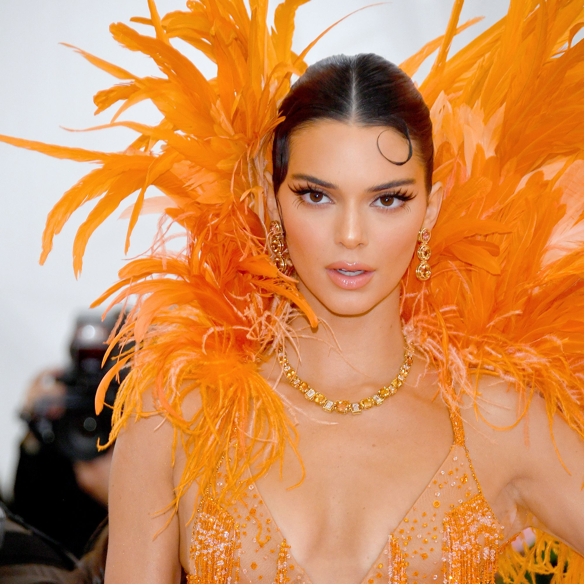 Kendall Jenner Jenner wore her hair slicked back in a chignon (with a tendril carefully curled on her forehead), extra long false lashes, and dewy, plumped up skin.