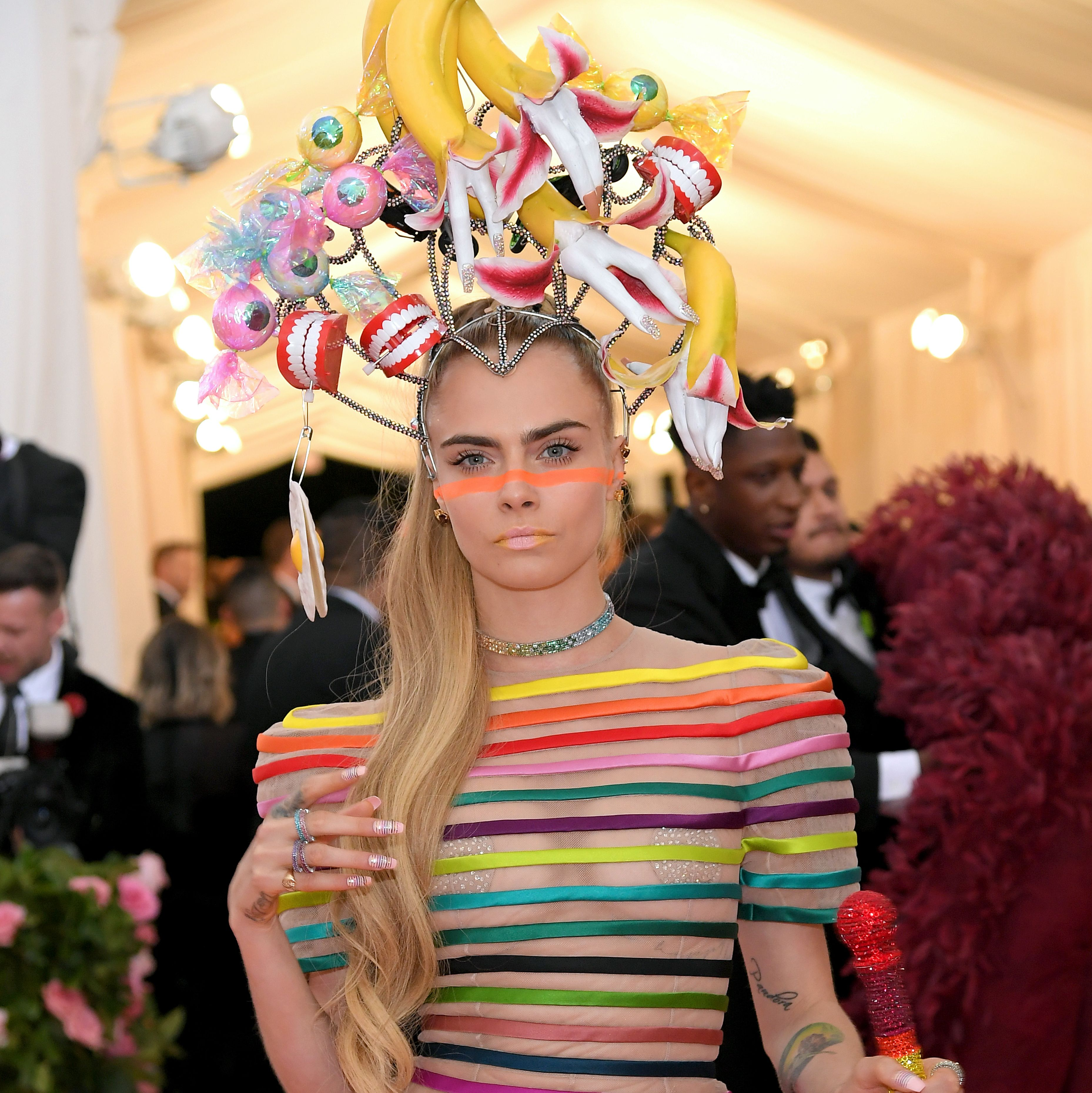 Cara Delevingne Delevingne went with a minimalist makeup look—save for an orange stripe across her face and yellow on her lips. An extra long blonde high pony anchored the dramatic headpiece.