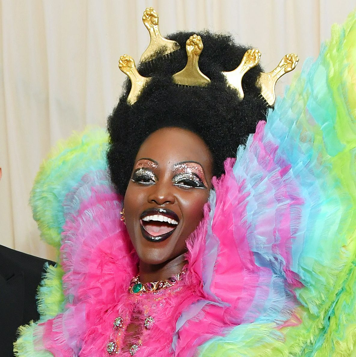 Lupita Nyong'o Nyong'o is a major winner of the night with a high afro decorated with golden picks. Her makeup featured a cut crease, glitter eye look with bold, black lacquer lips.