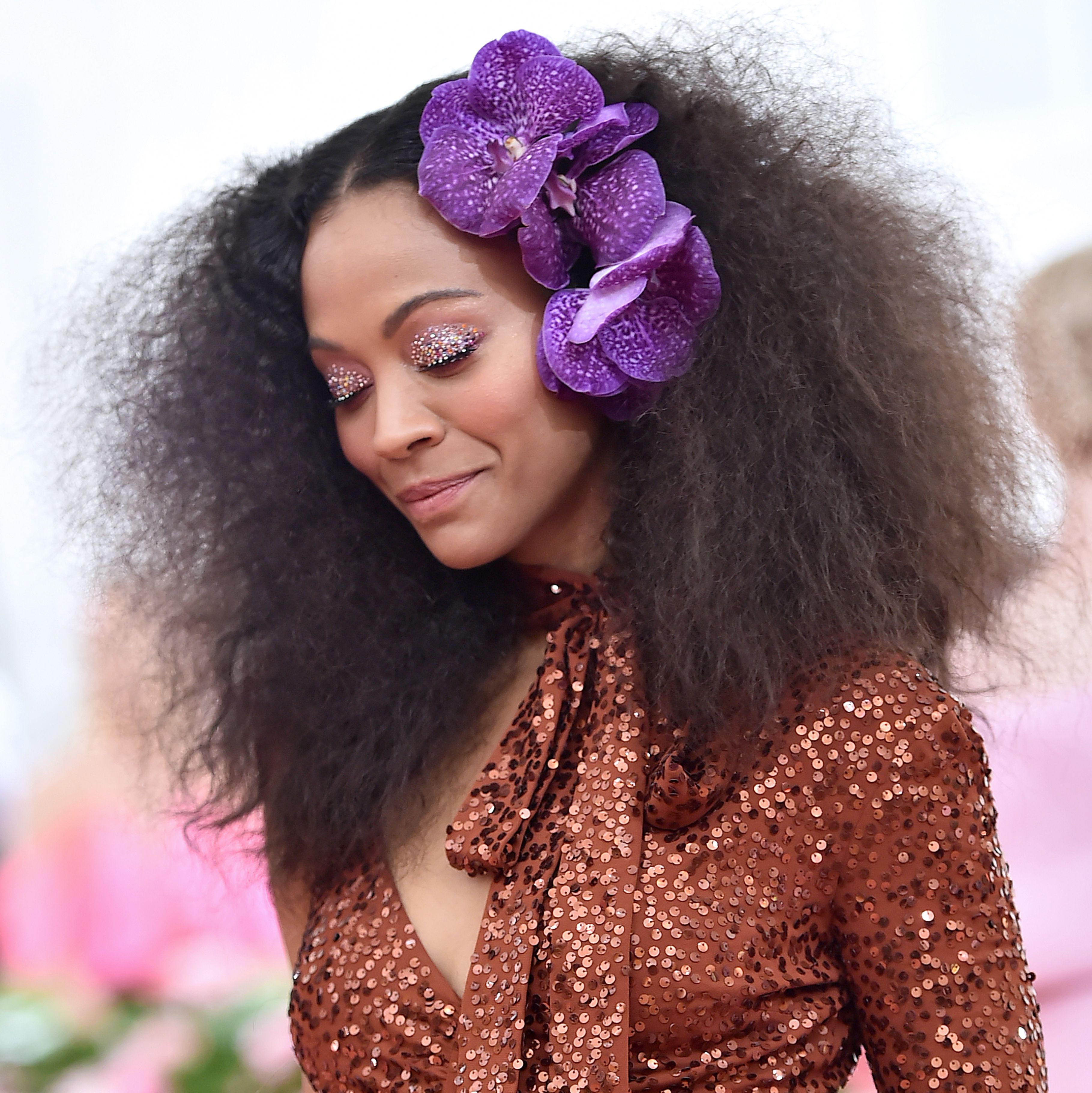 Zoe Saldana The actress looked glorious in brushed out curls and actual violet orchids in her hair. When she turned her eyes downward, you could see they had a gorgeous glitter overlay.