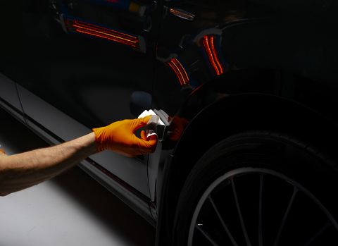 car polish wax worker hands polishing car buffing and polishing vehicle with ceramic car detailing man holds a polisher in the hand and polishes the car with nano ceramic tools for polishing