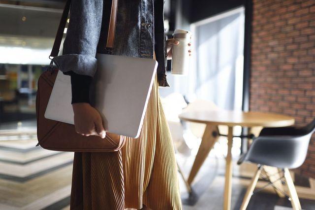 mujer en la oficina llevando un portátil y un café
