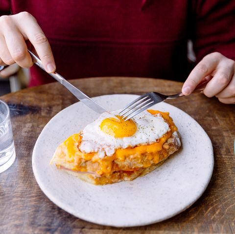 man eating croque madame sandwich with cheese and fried egg  mens health saturated fat