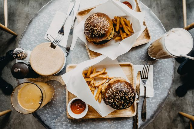 top view of burgers with french fries and drinks freshly served on table in cafe