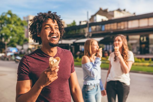 man in focus, eating ice cream on a beautiful day with her friends