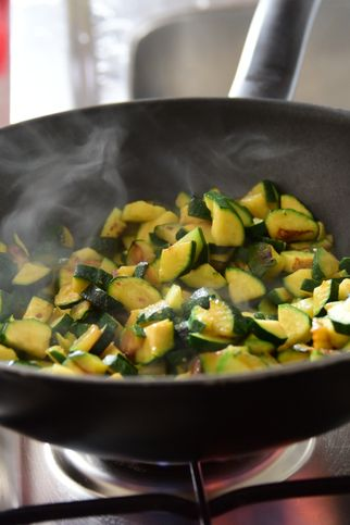 close up of a pan on an open flame gas cooker, sautéing courgettes