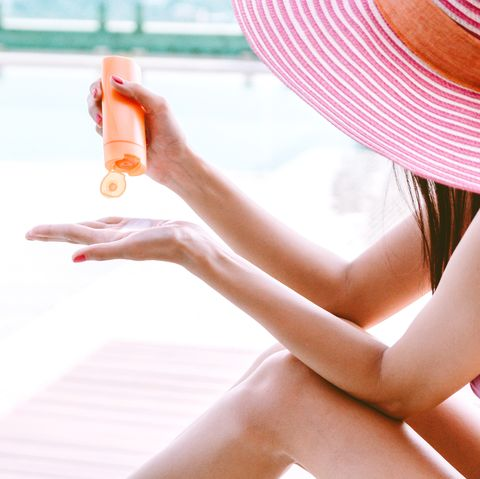 Midsection Of Woman With Sunscreen By Swimming Pool