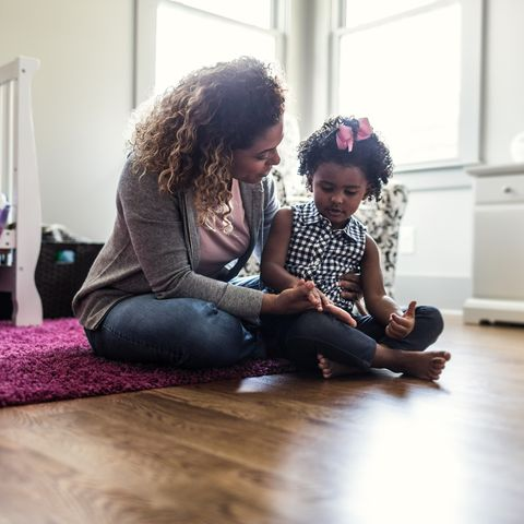 Mother and daughter playing on bedroom floor