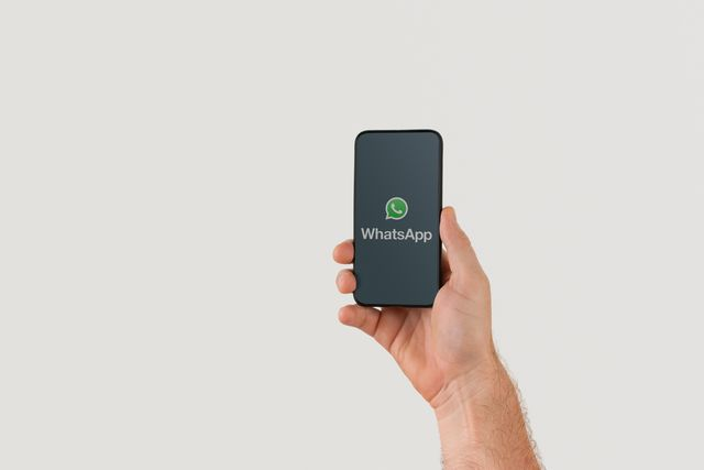 hand holding smart phone with popular online text  call application whatsapp logo on screen illustrative editorial image with copy space for text