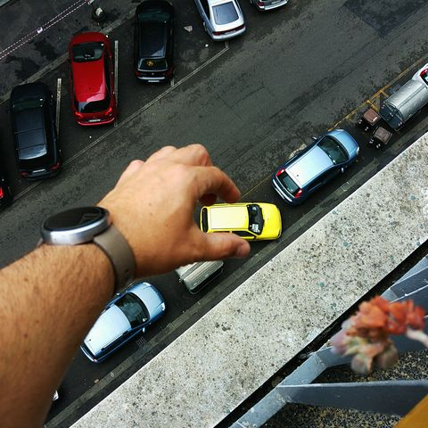 Optical Illusion Of Man Hand Holding Yellow Car On Street In City