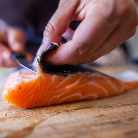 This photo shows a person in the kitchen cutting fish, including salmon, a cobblestone