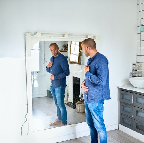 mixed race man in his 40s with concerned expression looking at reflection, losing weight, body concern, body conscious