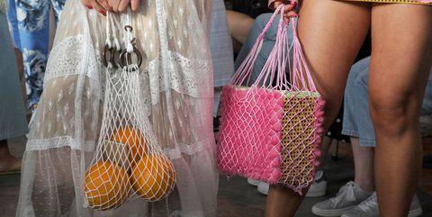 vrouwen dragen plastic nettassen tijdens fashion show