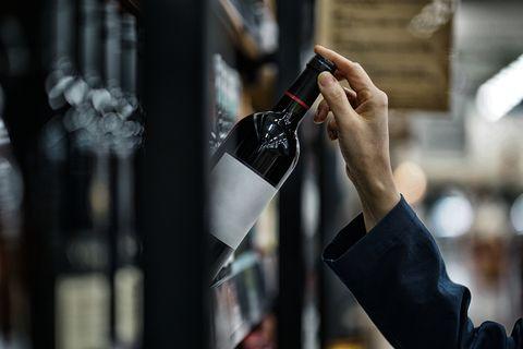 Woman choosing wine bottle in liquor store