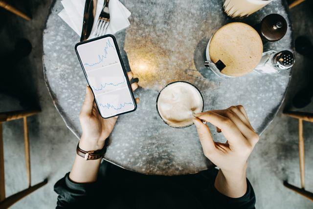 mujer tomando café y revisando sus facturas
