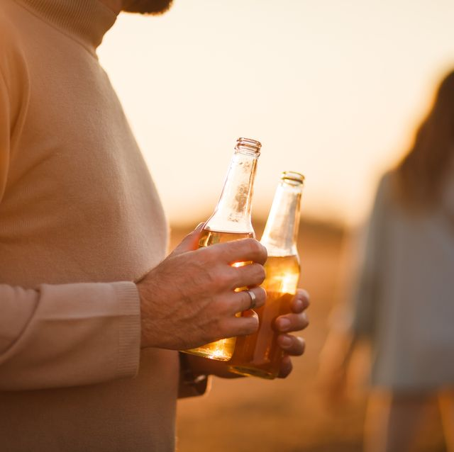 Man holding two drinks outdoors
